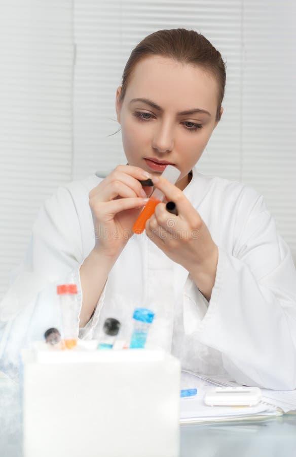 O retrato de um cientista novo etiqueta o tubo para o teste ou o ensaio imagens de stock