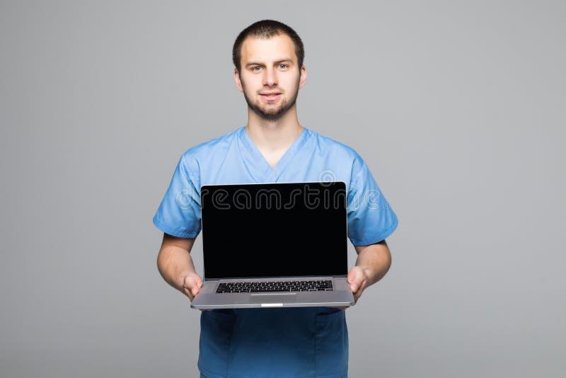 O retrato de um doutor masculino feliz vestiu-se no uniforme com o estetoscópio que mostra o laptop da tela vazia isolado sobre o imagem de stock royalty free