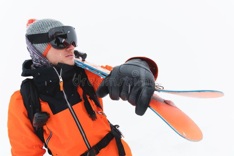 O retrato de um esquiador profissional do atleta em um revestimento alaranjado que veste uma máscara preta e com os esquis em seu fotografia de stock