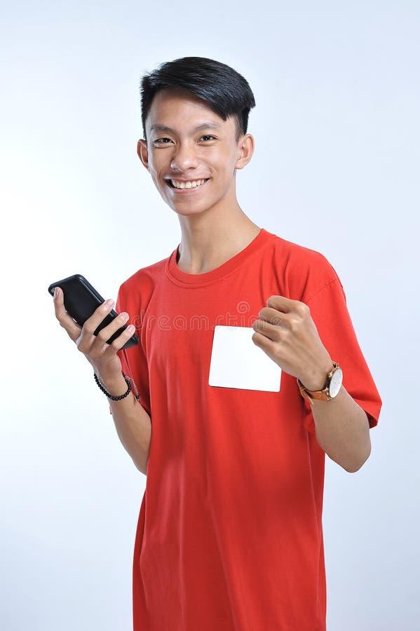 O retrato de um homem asiático do estudante novo que fala no telefone celular, fala o sorriso feliz fotos de stock royalty free