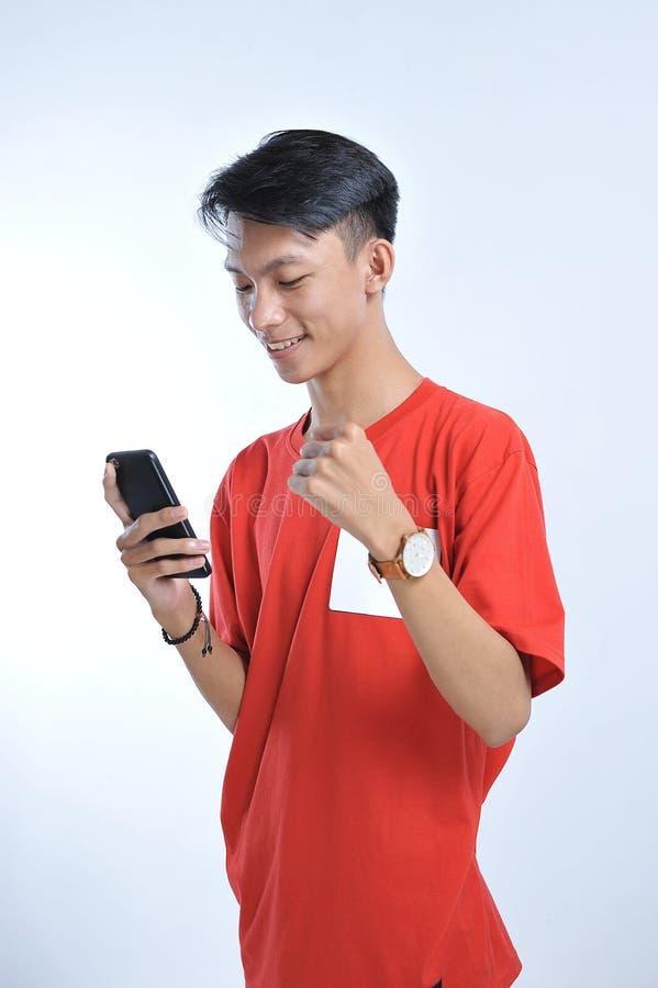 O retrato de um homem asiático do estudante novo que fala no telefone celular, fala o sorriso feliz foto de stock