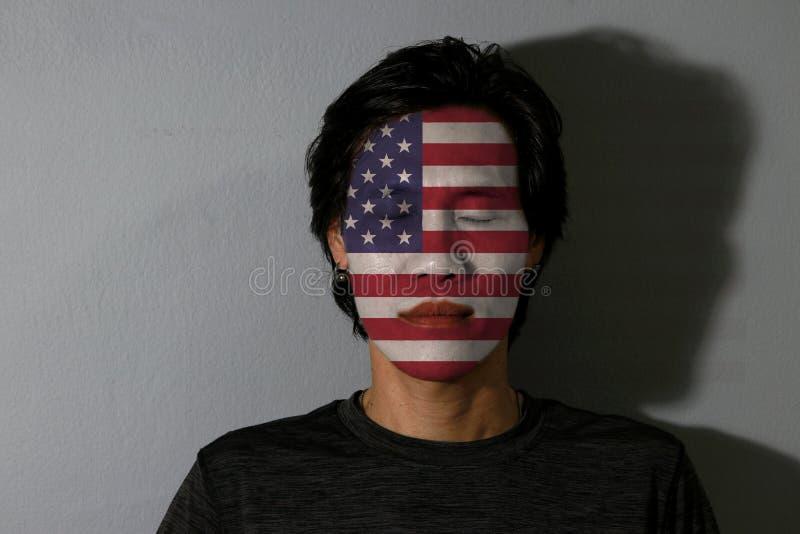 O retrato de um homem com a bandeira da América pintou em seus cara e olhos próximos com sombra preta no fundo cinzento foto de stock