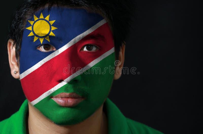 O retrato de um homem com a bandeira da Namíbia pintou em sua cara no fundo preto foto de stock