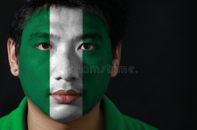 O retrato de um homem com a bandeira da Nigéria pintou em sua cara no fundo preto foto de stock royalty free