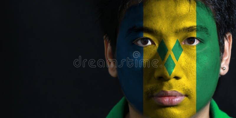 O retrato de um homem com a bandeira do Saint Vincent pintou em sua cara no fundo preto imagem de stock