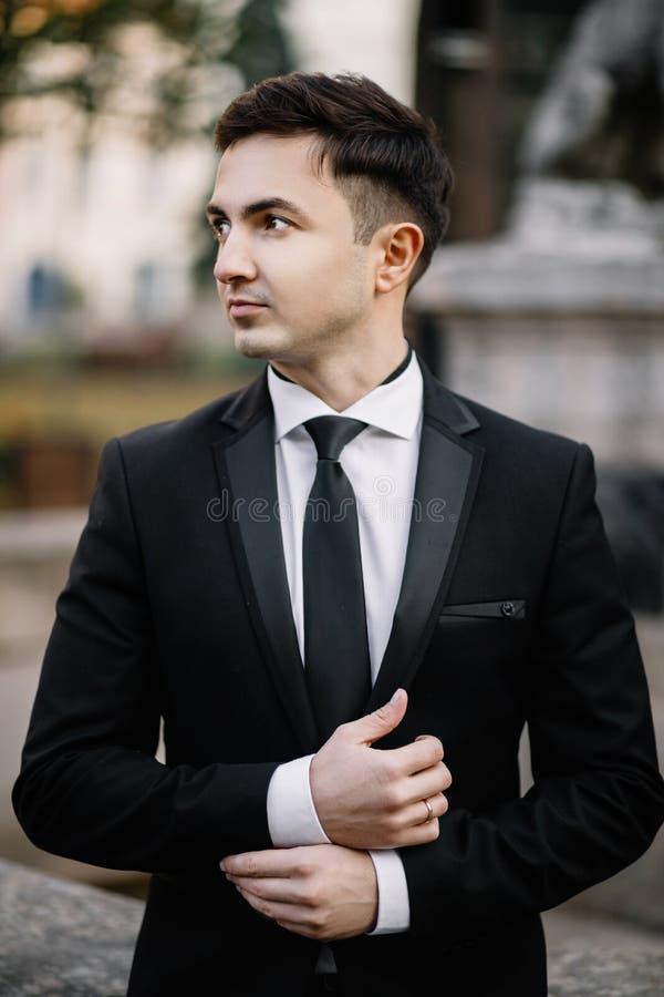 O retrato de um homem considerável novo sério vestiu-se no preto, drama foto de stock