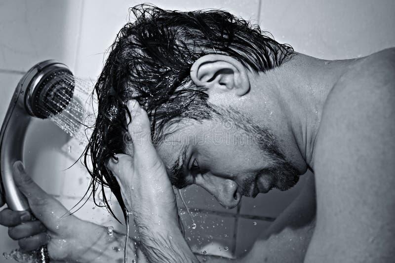 O retrato de um homem considerável novo toma um chuveiro fotografia de stock
