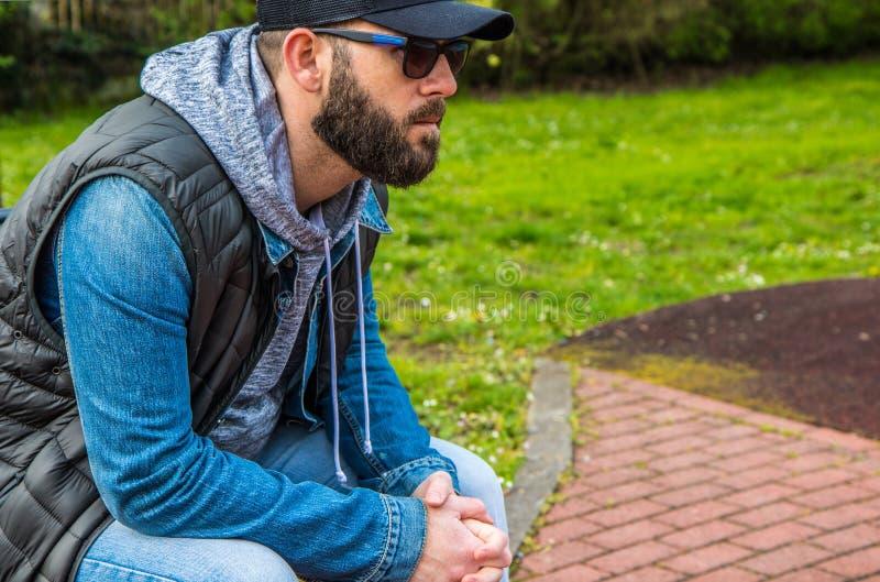 O retrato de um homem farpado com óculos de sol e o chapéu sentam-se no banco em um parque foto de stock royalty free