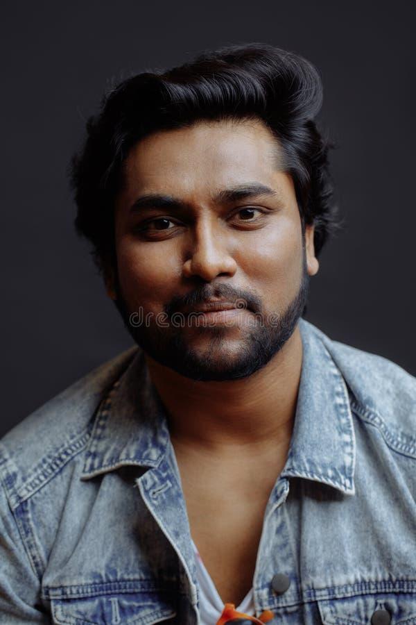 O retrato de um homem indiano lindo vestiu-se no revestimento da sarja de Nimes isolado imagem de stock royalty free