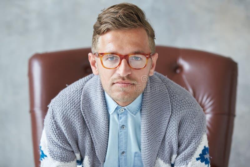 O retrato de um homem inteligente à moda com vidros olha fixamente na câmera, boa vista, camisa não barbeado, carismática, azul p fotografia de stock