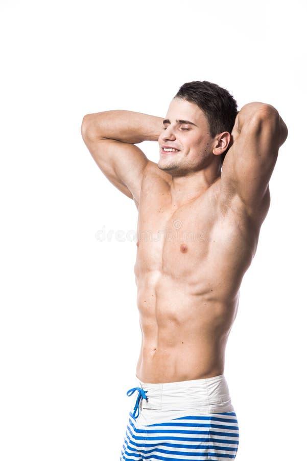 O retrato de um homem muscular novo considerável no roupa de banho com mãos dobrou sua vista isolada cabeça acima eyes fechado so fotos de stock