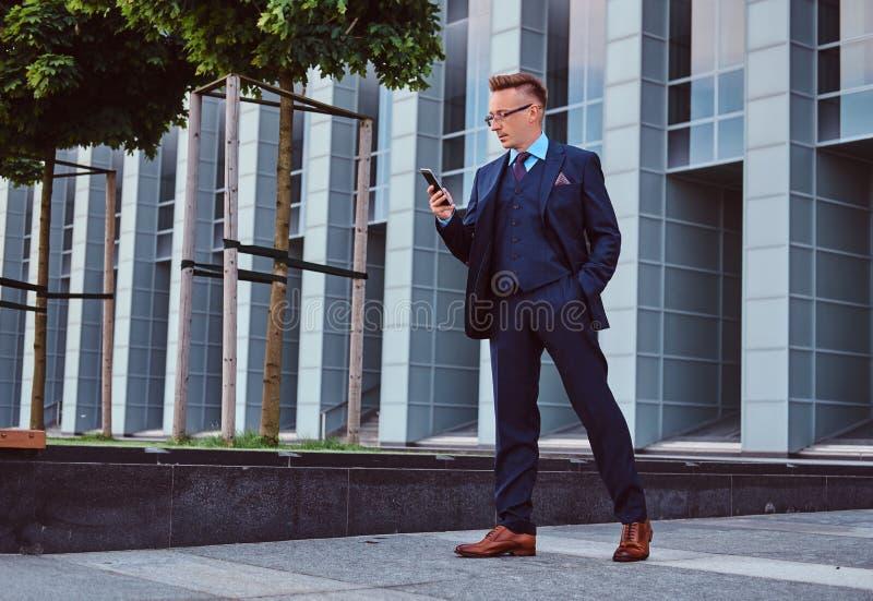 O retrato de um homem de negócios à moda seguro vestiu-se em um terno elegante usando um smartphone ao estar fora imagem de stock royalty free