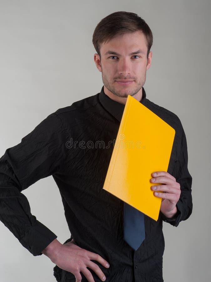 O retrato de um homem de negócios bem sucedido com um dobrador para o amarelo faz imagens de stock