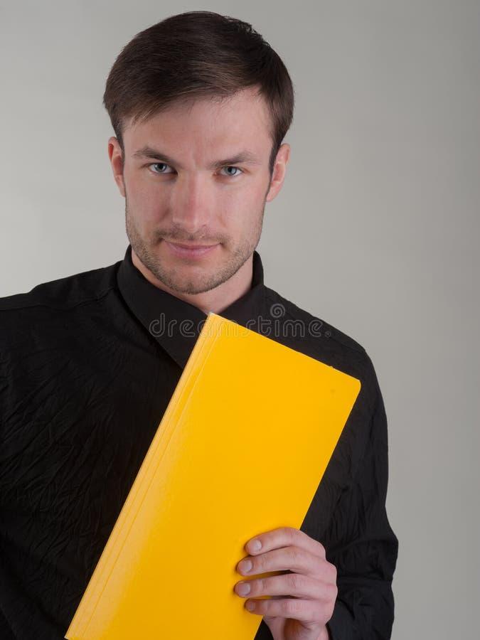 O retrato de um homem de negócios bem sucedido com um dobrador para o amarelo faz fotografia de stock
