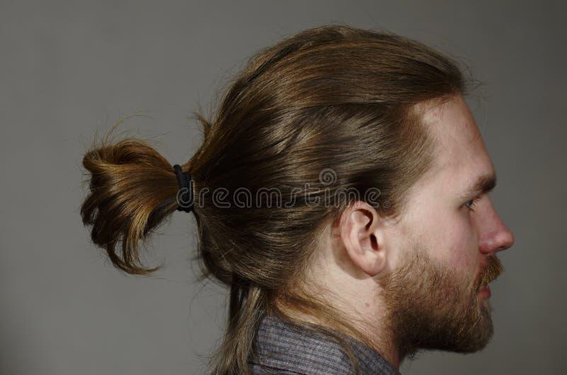 O retrato de um homem novo com uma barba e o bigode tomam partido sobre a obscuridade fotos de stock