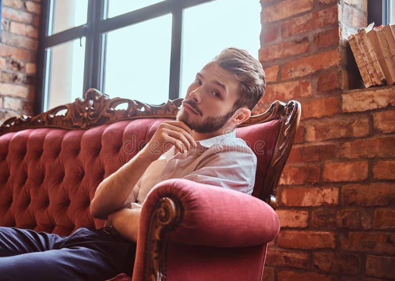 O retrato de um homem novo considerável com uma barba e um cabelo à moda vestiu elegantemente o assento em um sofá vermelho do vi fotografia de stock royalty free