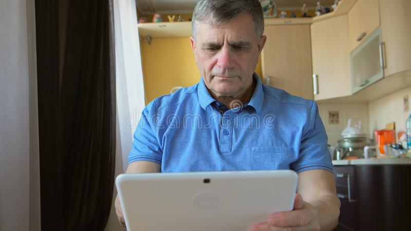 O retrato de um homem superior senta e datilografa um PC da tabuleta em casa imagens de stock