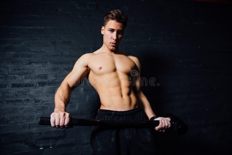 O retrato de um jovem coube fisicamente o exercício do homem no gym com o martelo atlético muscular foto de stock
