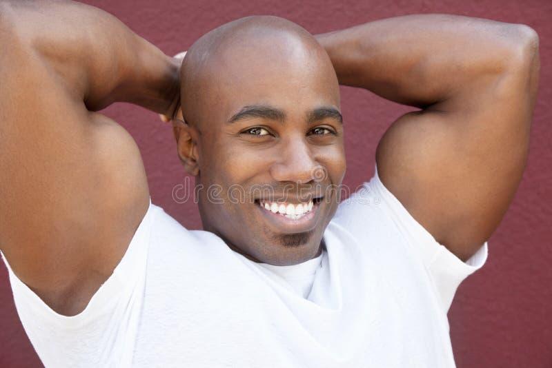 O retrato de um jovem coube fisicamente o homem afro-americano com as mãos atrás da cabeça fotografia de stock royalty free