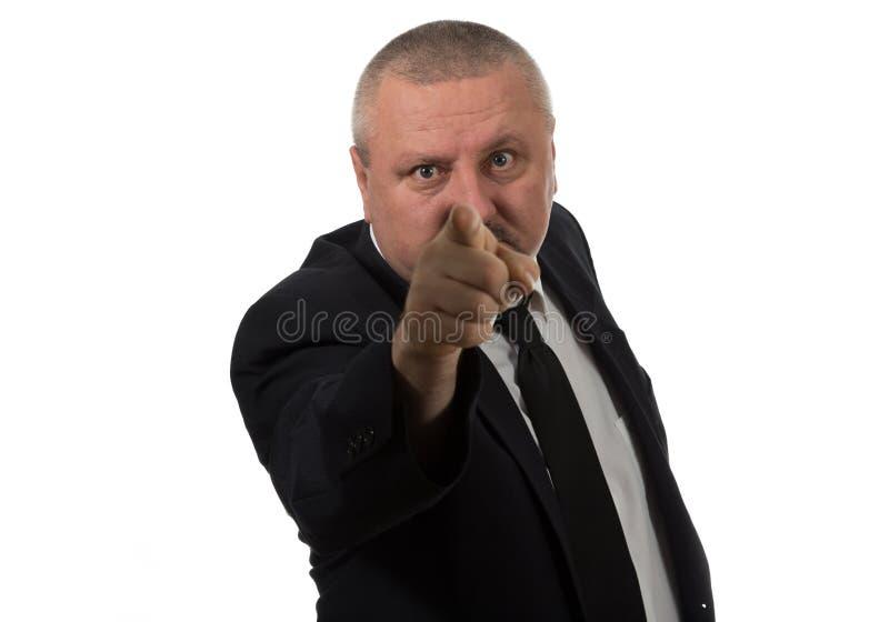 O retrato de um meio irritado envelheceu o homem de negócios no terno que aponta em você fotos de stock royalty free
