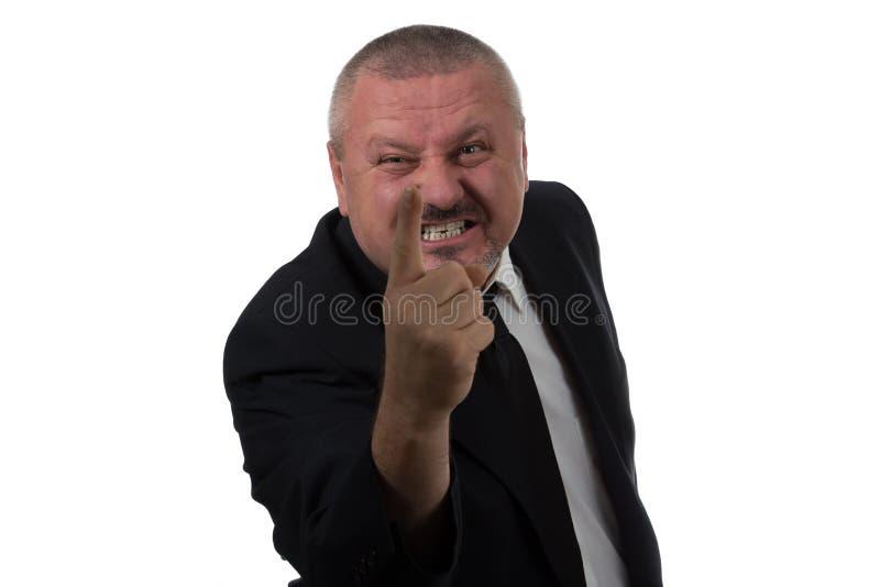 O retrato de um meio irritado envelheceu o homem de negócios no terno que aponta em você fotos de stock