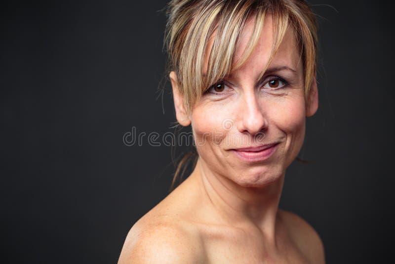 O retrato de um meio de sorriso envelheceu a mulher caucasiano contra o fundo escuro fotos de stock royalty free