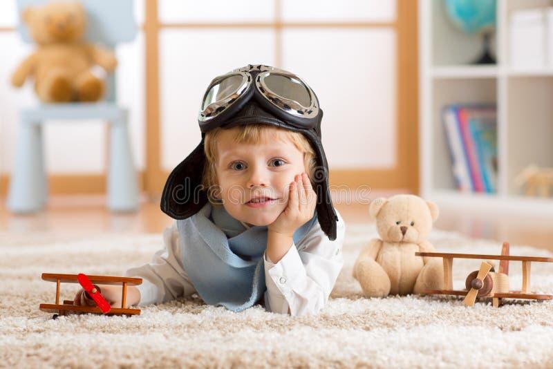 O retrato de um menino da criança que joga com avião de madeira e que sonha seja aviador fotografia de stock royalty free