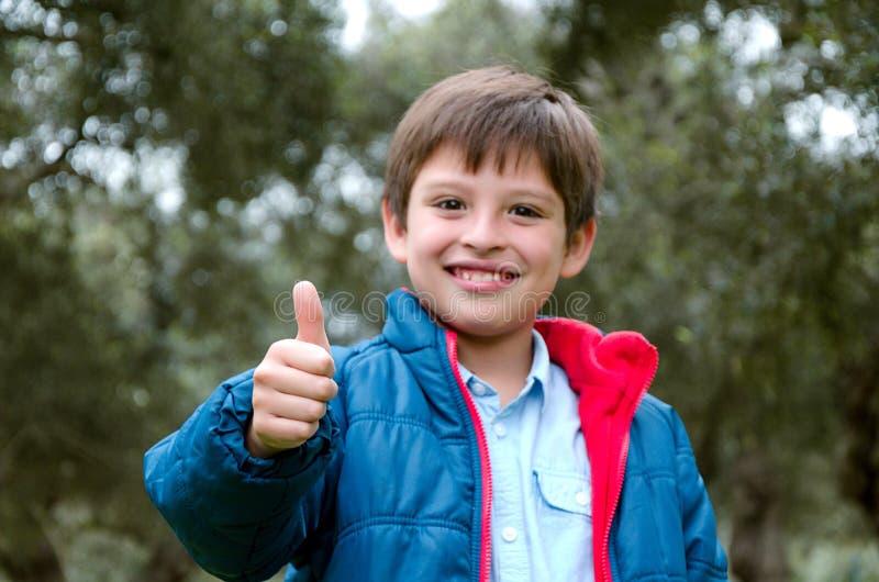 O retrato de um menino louro-de cabelo bonito, polegares levanta e sorri imagem de stock