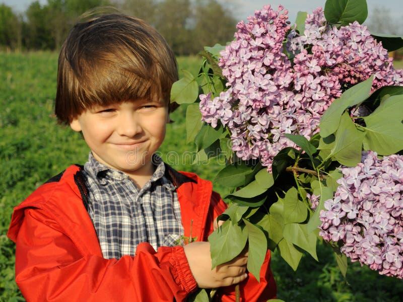 O retrato de um menino novo de sorriso com o lilás no seu entrega 1 imagem de stock royalty free