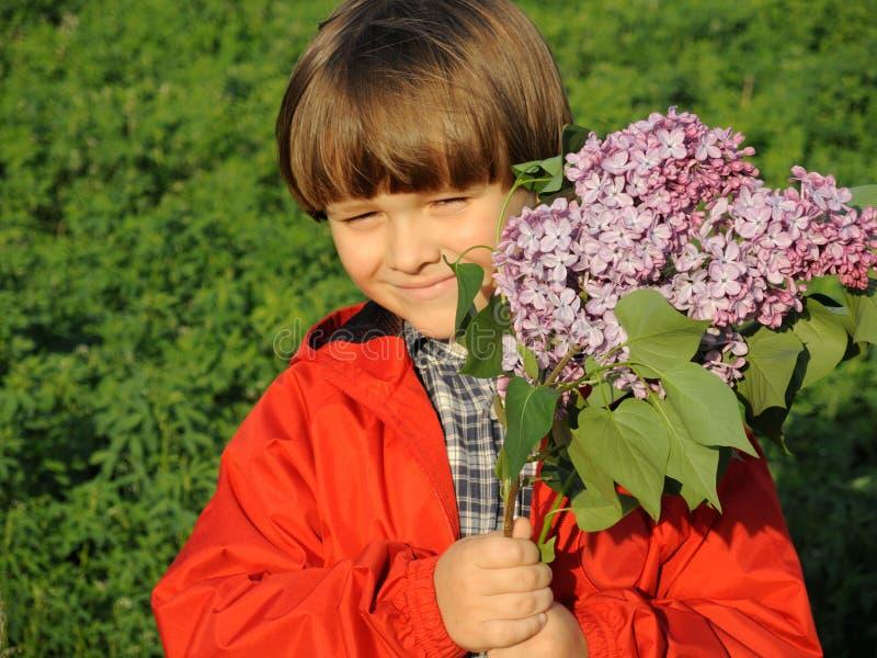 O retrato de um menino novo de sorriso com o lilás no seu entrega 1 foto de stock