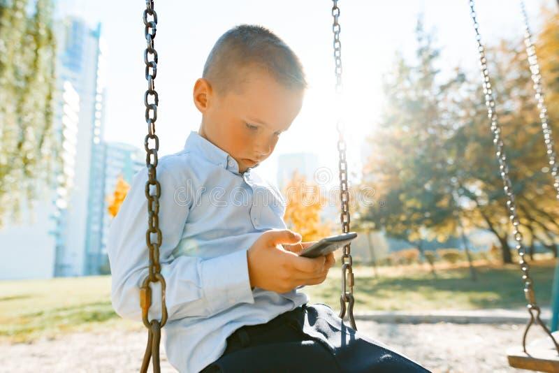 O retrato de um menino de sorriso 6, 7 anos velhos, criança monta um balanço no parque do outono, hora dourada fotografia de stock