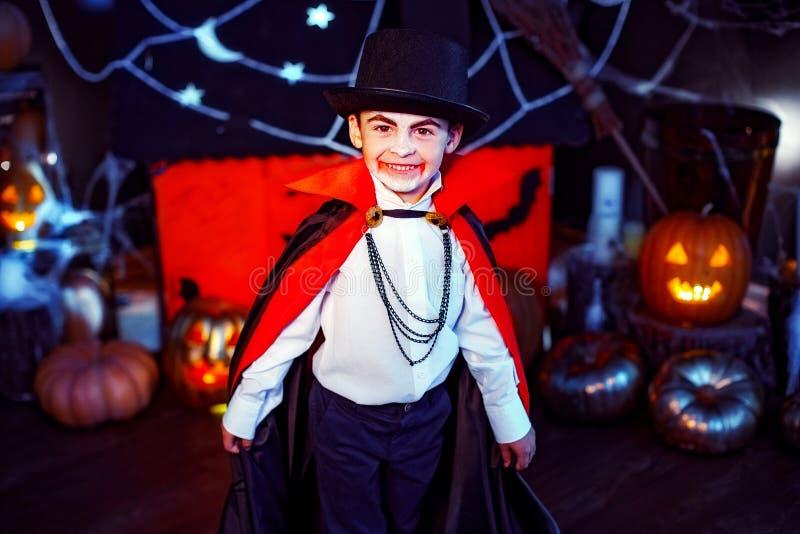 O retrato de um menino vestiu-se em um traje de um vampiro sobre o fundo do grunge fotografia de stock royalty free