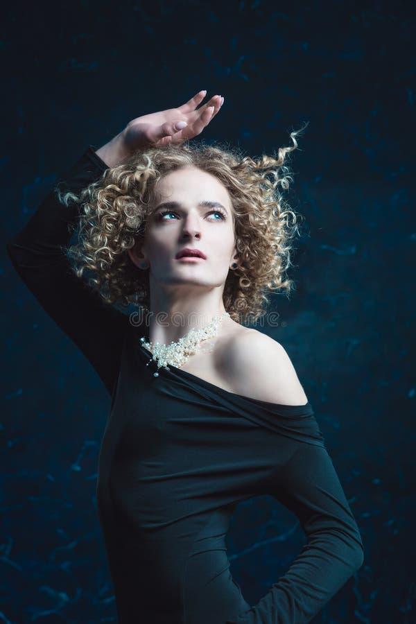 O retrato de um modelo do indivíduo do transgender com olhos azuis e cabelo louro na imagem de uma menina com os grânulos em torn fotografia de stock royalty free