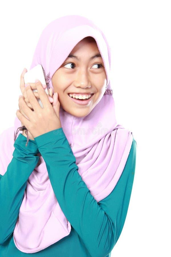 O retrato de um muçulmano asiático caçoa a fala no telefone celular fotos de stock