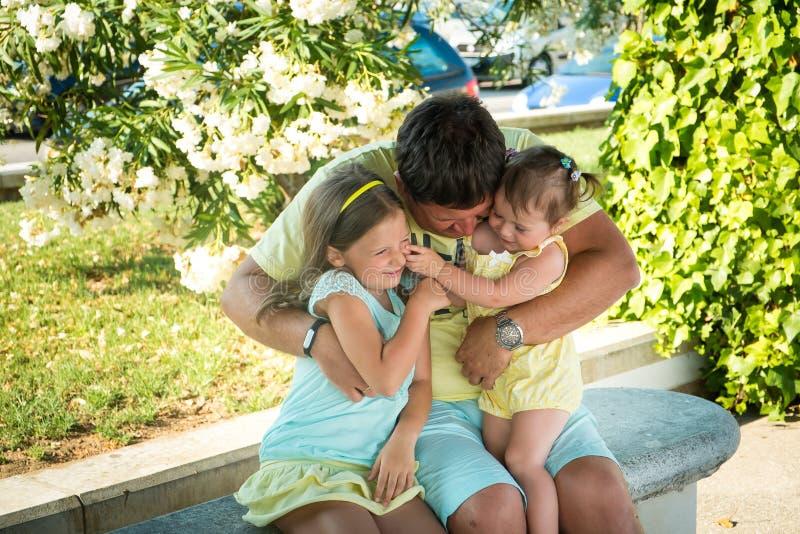 O retrato de um pai e duas filhas pequenas em um verão estacionam imagem de stock royalty free