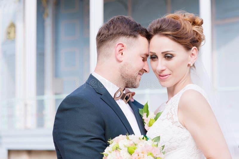 O retrato de um par bonito de recém-casados é abraçado contra o contexto de uma construção do vintage da exposição foto de stock