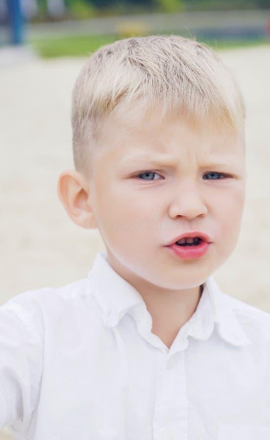 O retrato de um pouco desagradou e descontentou o menino com o cabelo louro dourado no dia de verão ensolarado no verde borrado foto de stock