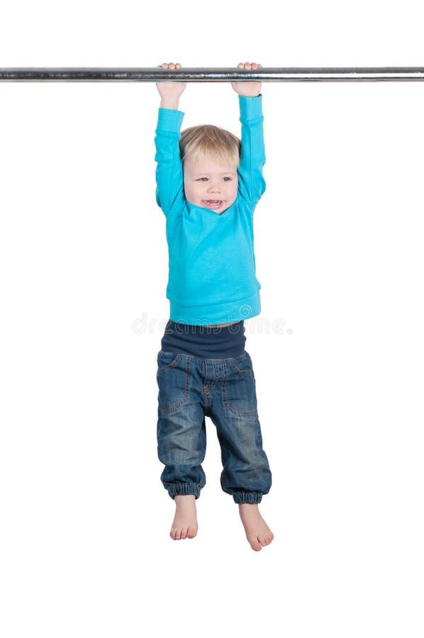 O retrato de um rapaz pequeno pendura pela barra horizontal imagens de stock