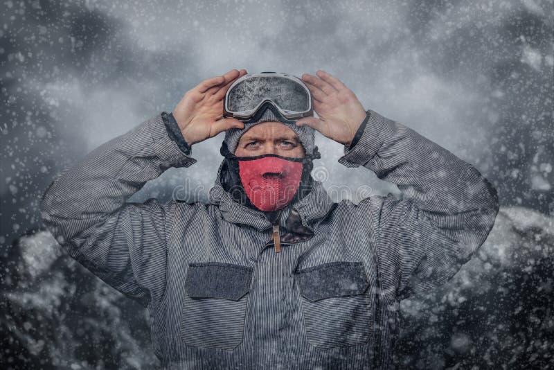 O retrato de um snowboarder vestido em uma engrenagem protetora completa para a snowboarding do extream põe sobre vidros ao estar foto de stock