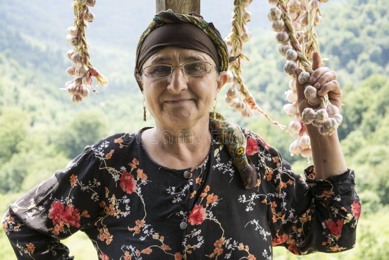 O retrato de uma colheita idosa da mulher secou o alho da fila no balco imagem de stock