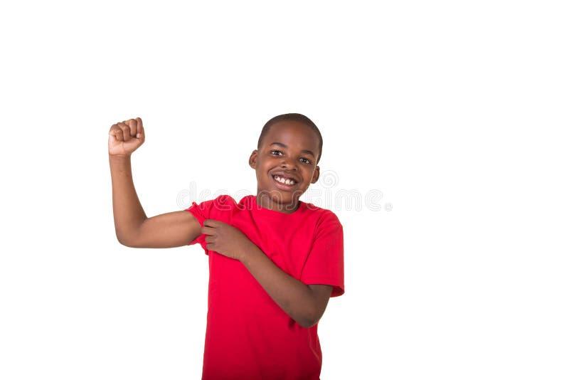 O retrato de uma escola envelheceu o menino que faz um músculo imagens de stock