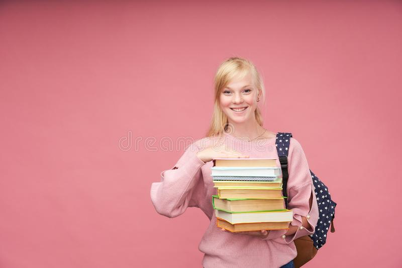 O retrato de uma estudante bonita com uma trouxa e de uma pilha de livros em suas mãos está sorrindo no fundo cor-de-rosa imagens de stock