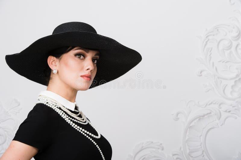 O retrato de uma jovem mulher bonita no estilo retro em um chapéu negro elegante e o vestido sobre rococós luxuosos muram o fundo imagens de stock royalty free