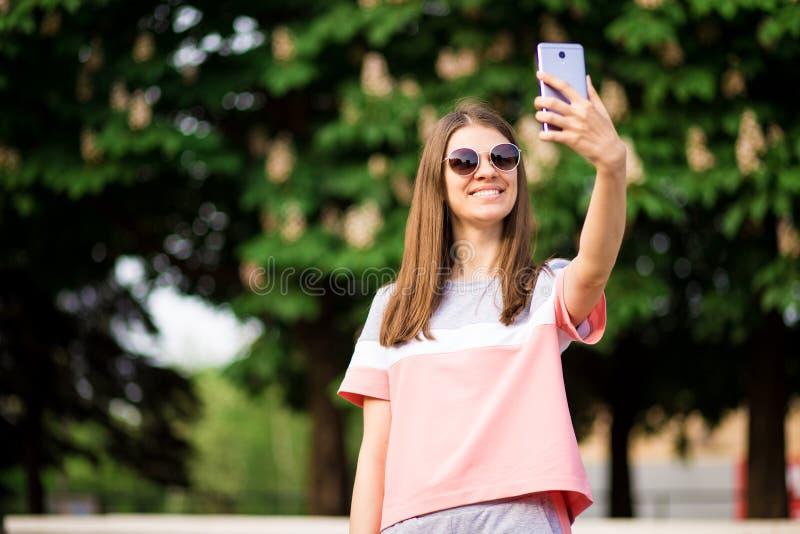 O retrato de uma jovem mulher bonita nos óculos de sol toma o selfie com um smartphone fotografia de stock