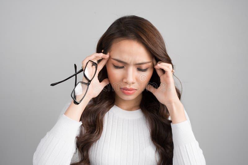 O retrato de uma jovem mulher tem uma dor de cabeça, enxaqueca isolada em g imagem de stock
