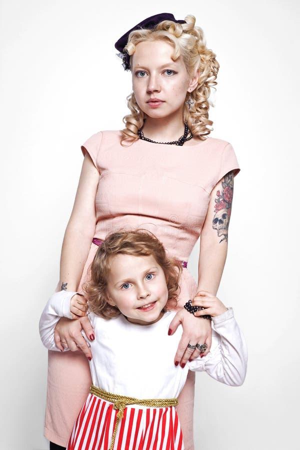 O retrato de uma mãe e de uma filha de aperto vestiu-se em vestidos bonitos no estilo retro imagens de stock