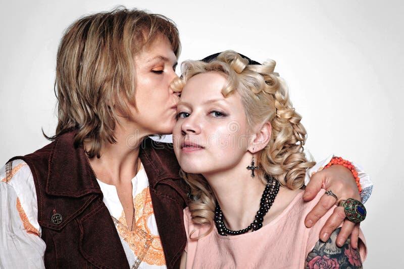 O retrato de uma mãe idosa de abraço e de uma filha adulta vestiu-se em vestidos bonitos no estilo retro foto de stock royalty free