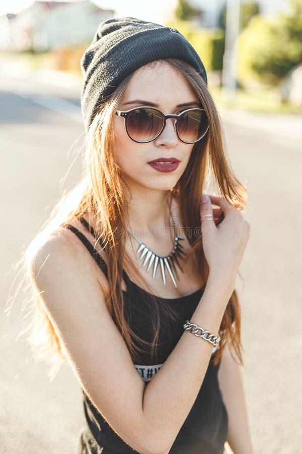 O retrato de uma menina à moda nova do moderno vestiu-se no tampão e em óculos de sol escuros imagem de stock royalty free