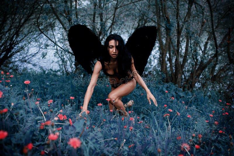 O retrato de uma menina bonita com preto voa um demônio foto de stock