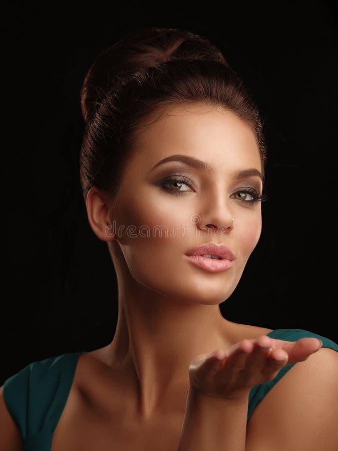 O retrato de uma menina bonita nova com cabelo recolhido e expressivo compõem no fundo preto enviam um beijo imagens de stock